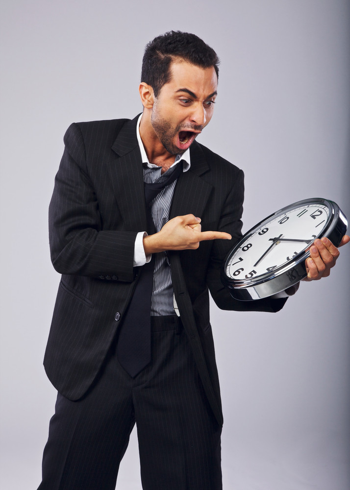 Angry businessman shouting and pointing to a clock