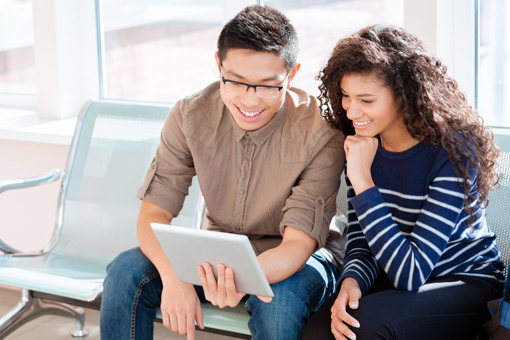 Asian boy and african american girl are using tablet computer