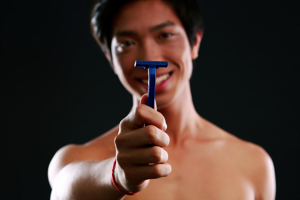 Asian man holding razor. Focus on razor