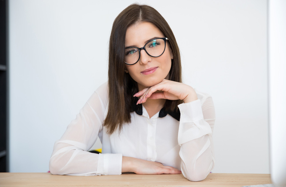 Attractive businesswoman sitting at the table in office