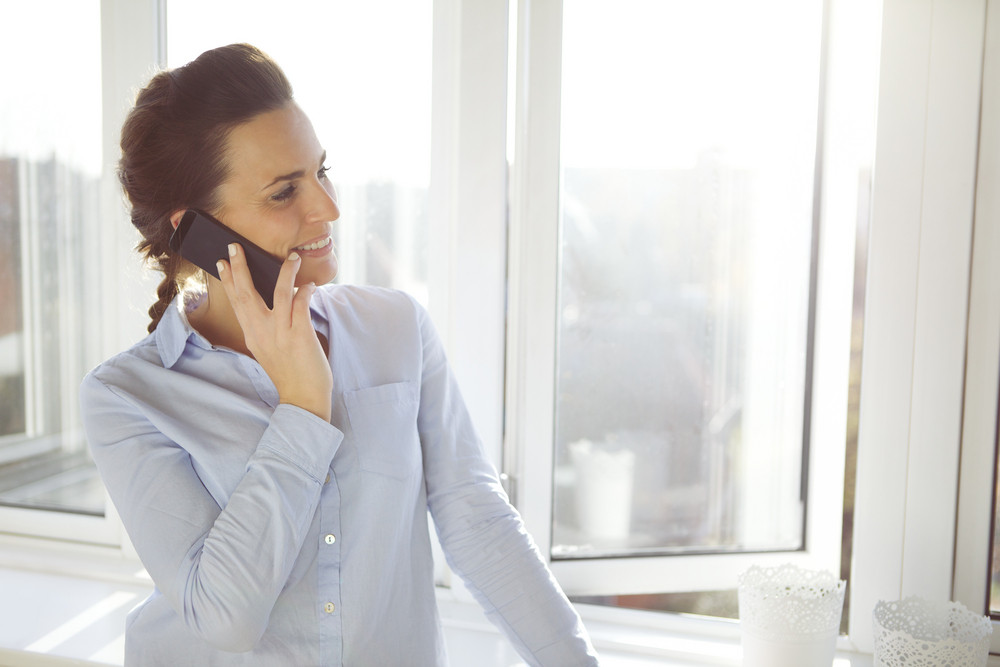 Attractive female executive standing in bright office talking on her mobile phone looking away smiling. Beautiful young caucasian business woman.