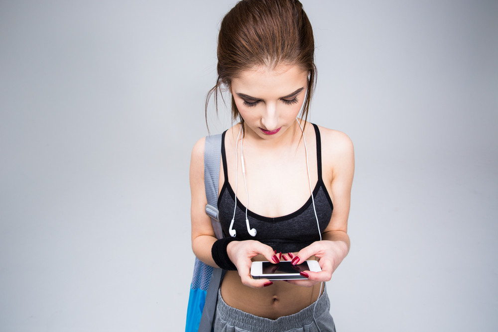 Attractive sporty woman using smartphone over gray background
