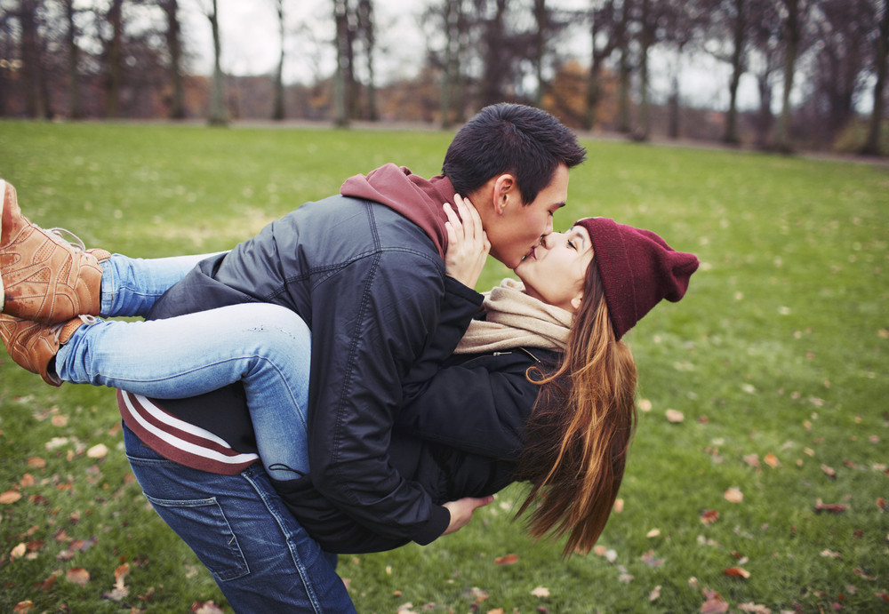 Attractive young man carrying his pretty girlfriend and kissing. Mixed race couple in love outdoors in park.