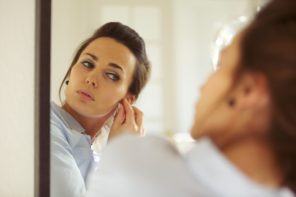 Attractive young woman putting on her earrings while looking at the mirror. Caucasian businesswoman getting dressed. Female model