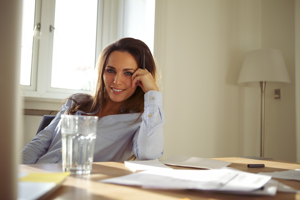 Attractive young woman sitting at her desk looking at camera smiling. Pretty caucasian businesswoman at home office desk working.