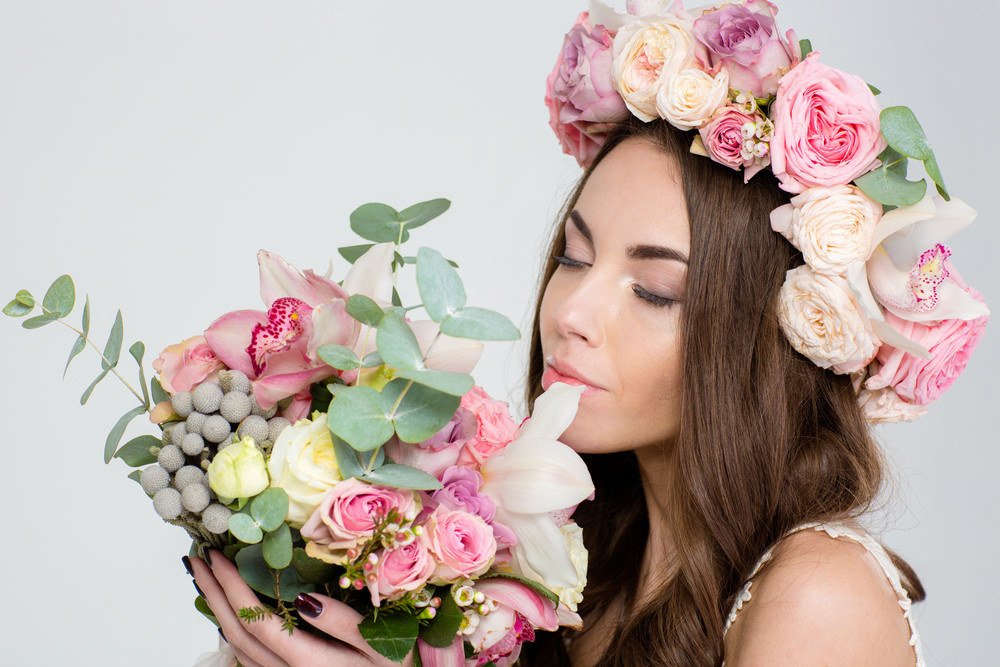 Attrative tender young woman in roses wreath holding and smelling beautiful bouquet of flowers over white background