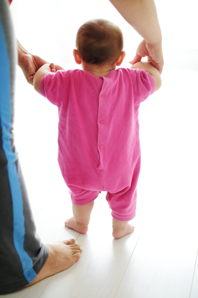Baby taking first steps with mother help on white background