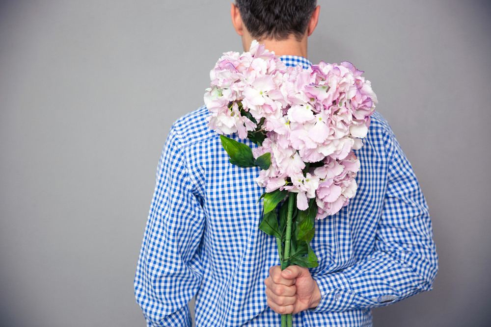 Back view portrait of a man standing with flowers