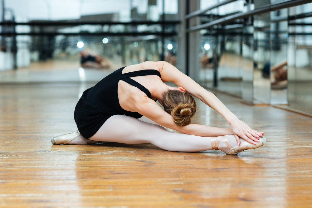 Ballet dancer performing exercise while sitting on floor