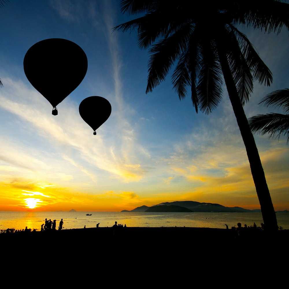 Balloon on Tropical beach with people in silhouette