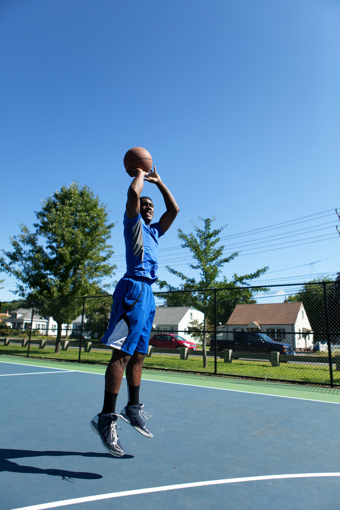Basketball player shooting the ball at the basket on an outdoor court.