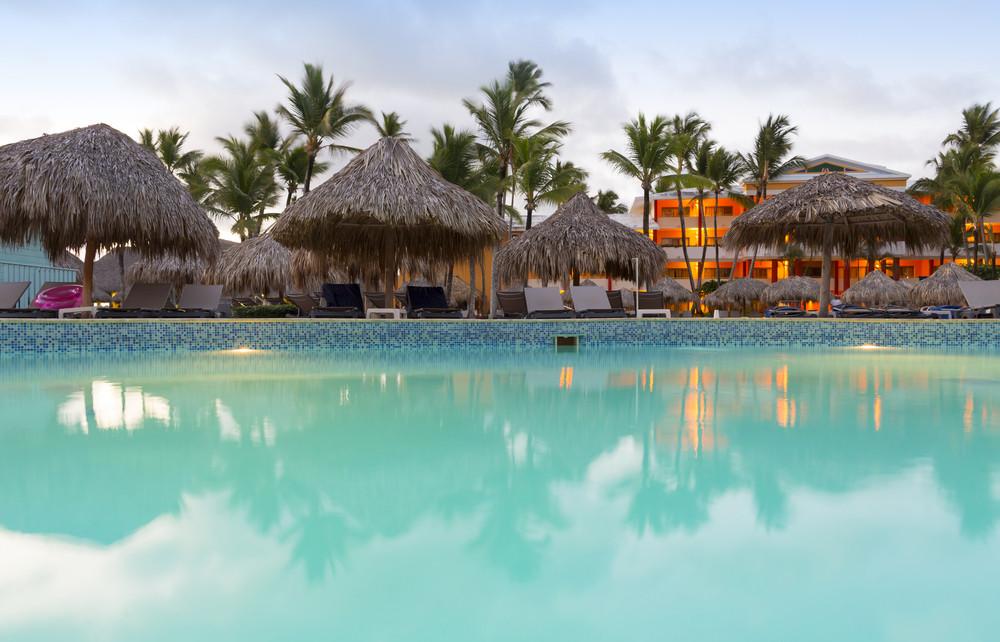 海灘傘和椅子沿著熱帶度假勝地的游泳池