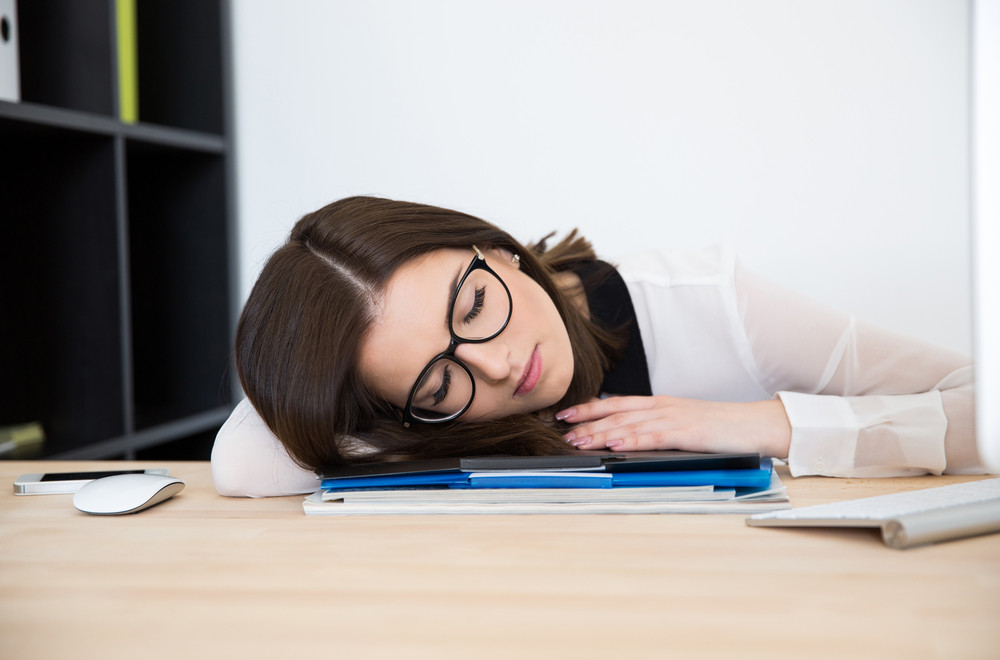 Beautiful businesswoman sleeping at the table in office