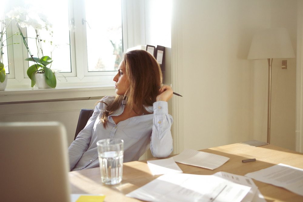 Beautiful caucasian female sitting at table with glass of water, documents and laptop. Business woman in home office looking away thinking.