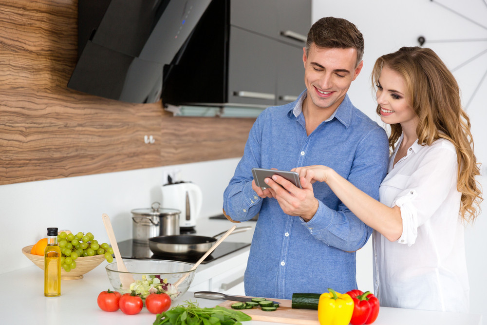 Beautiful couple using smartphone and cooking on the kitchen at home