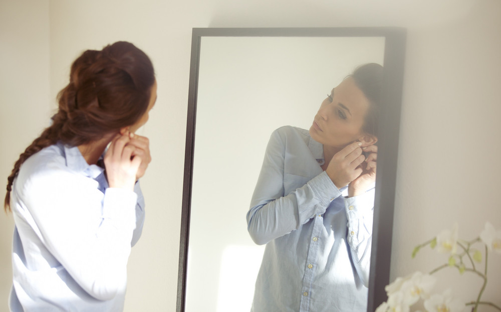 Beautiful female putting on her earring in front of mirror. Businesswoman getting dressed for work. Caucasian female model in blue shirt.
