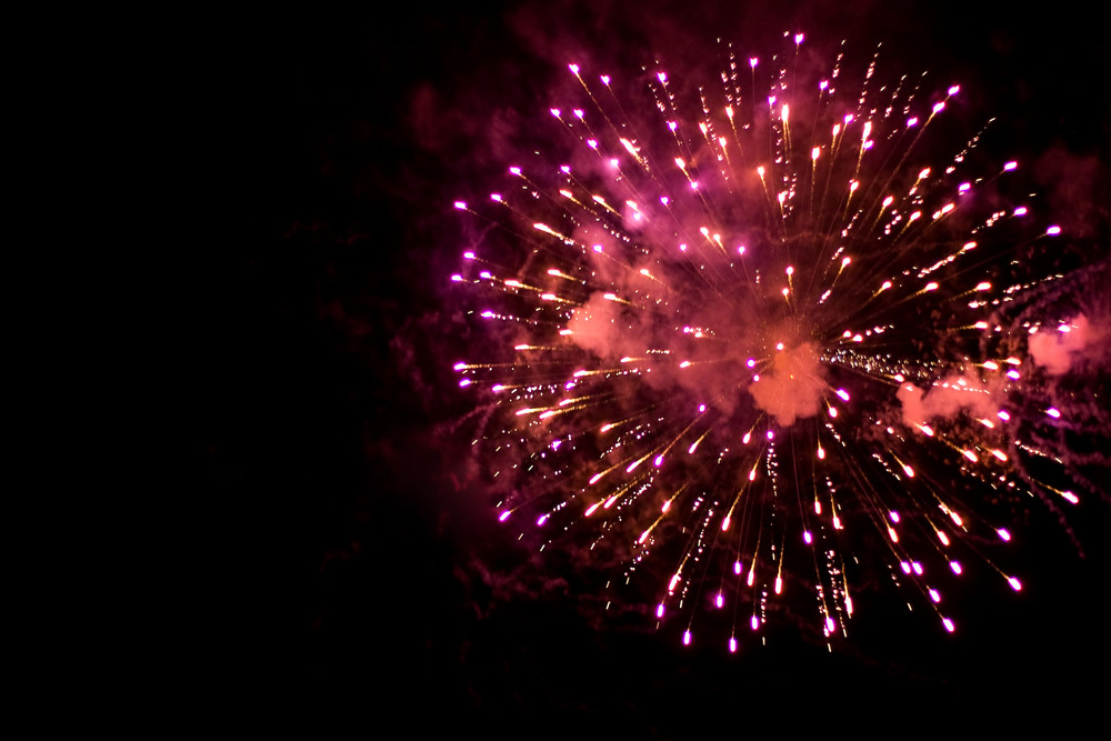 Beautiful fireworks exploding over a dark night sky.