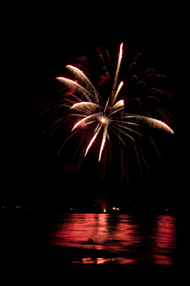Beautiful fireworks going off over the dark night sky reflecting over the water.