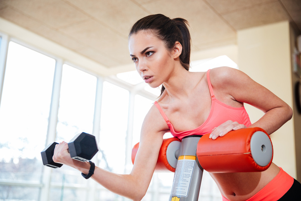 Beautiful focused young sportswoman working out with dumbbells in gym