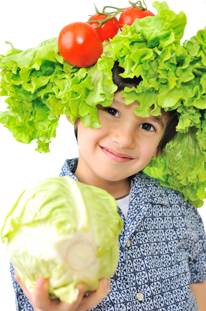 Beautiful little kid with tomato and salad hat on his head holding cabbage
