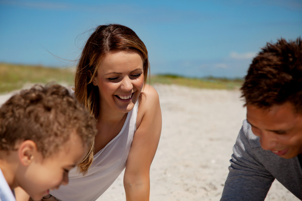 Beautiful mom looking happy in a weekend bonding with her son and husband on a beach