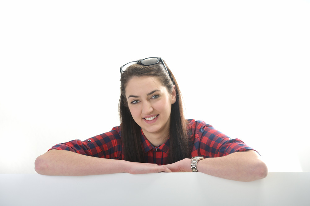 Beautiful smiling girl with checkered shirt isolated on whiteleaning on a blank banner