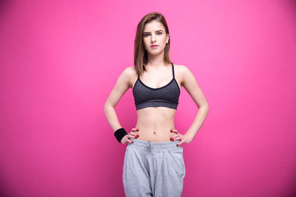 Beautiful sports woman standing over pink background