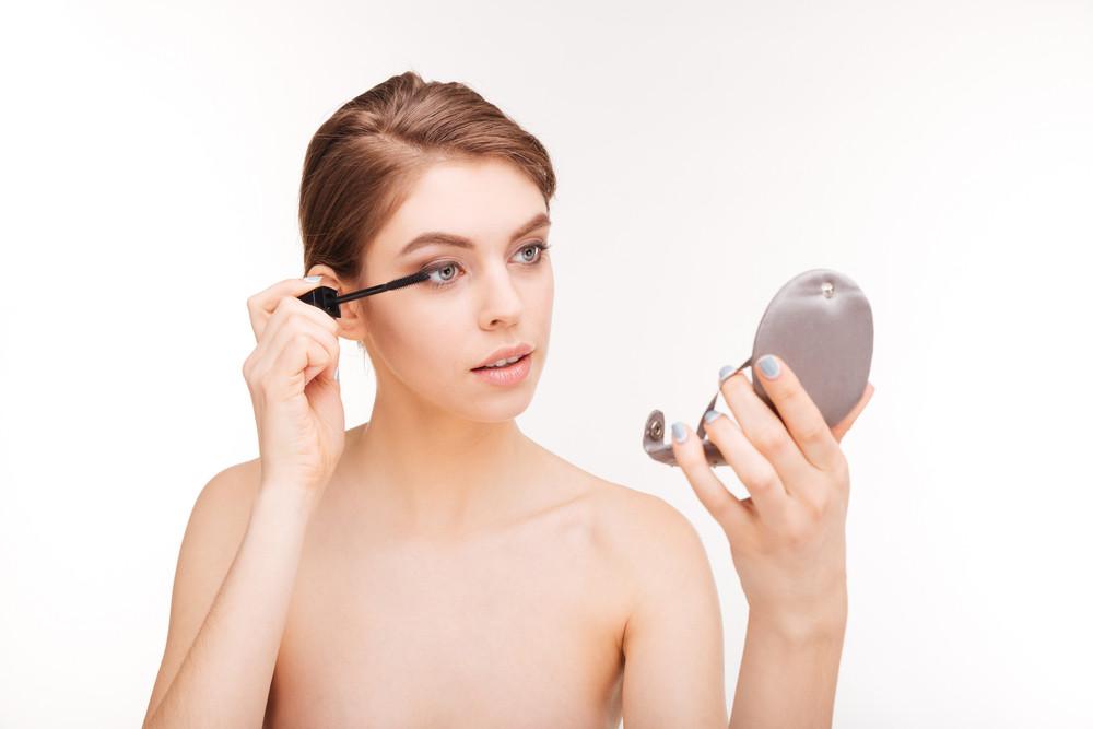 Beautiful woman applying mascara on her eyelashes isolated on a white background