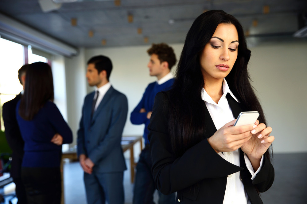 Beautiful woman using smartphone with colleagues on background
