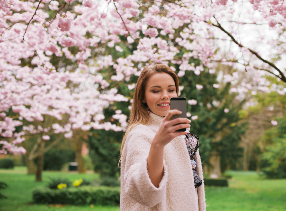 Beautiful young female taking pictures of with smartphone at spring blossom park. Caucasian female shooting at park with her mobile phone.