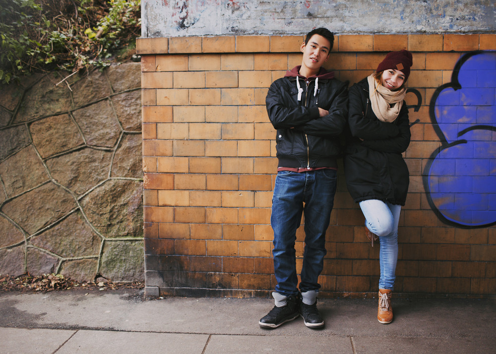 Beautiful young man and woman in warm clothes standing together leaning on a wall outdoors. Teenage asian couple posing at camera on street.