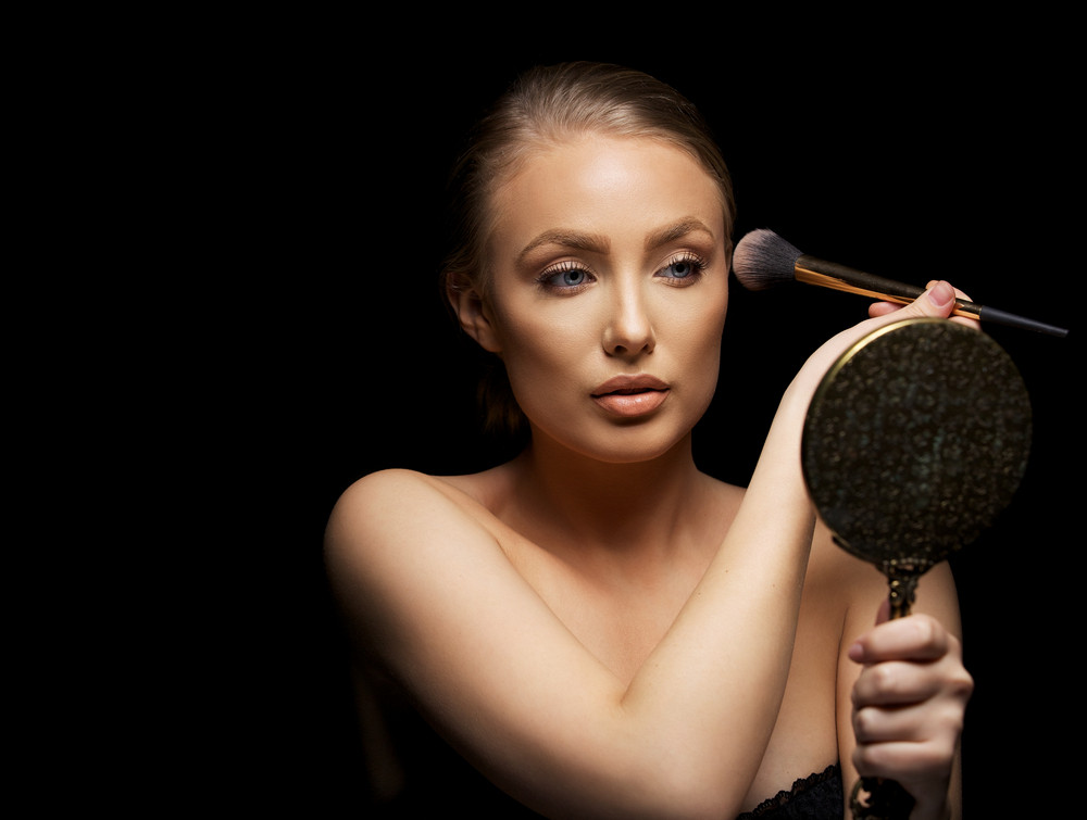 Beautiful young woman applying foundation on her face with a make up brush. Attractive young caucasian model with mirror against black background.