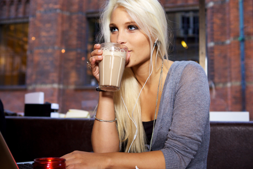 Beautiful young woman drinking a café latte.