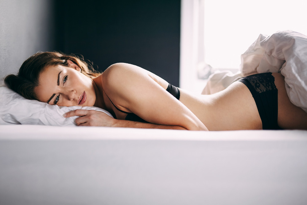 Beautiful young woman in lingerie lying in her bed looking away thinking. Thoughtful female model resting on bed.