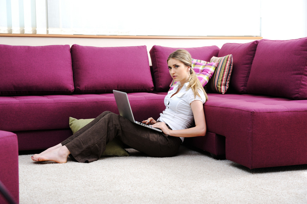 Beautiful young woman in living room on sofa using laptop