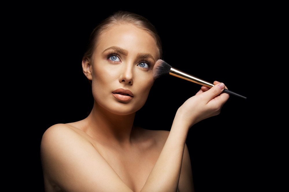Beautiful young woman looking away while applying makeup on her face. Blue bright eyes and clean soft skin.