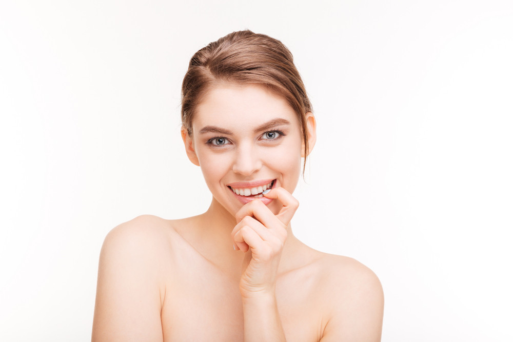 Beauty portrait of a happy woman with fresh skin looking at camera isolated on a white background