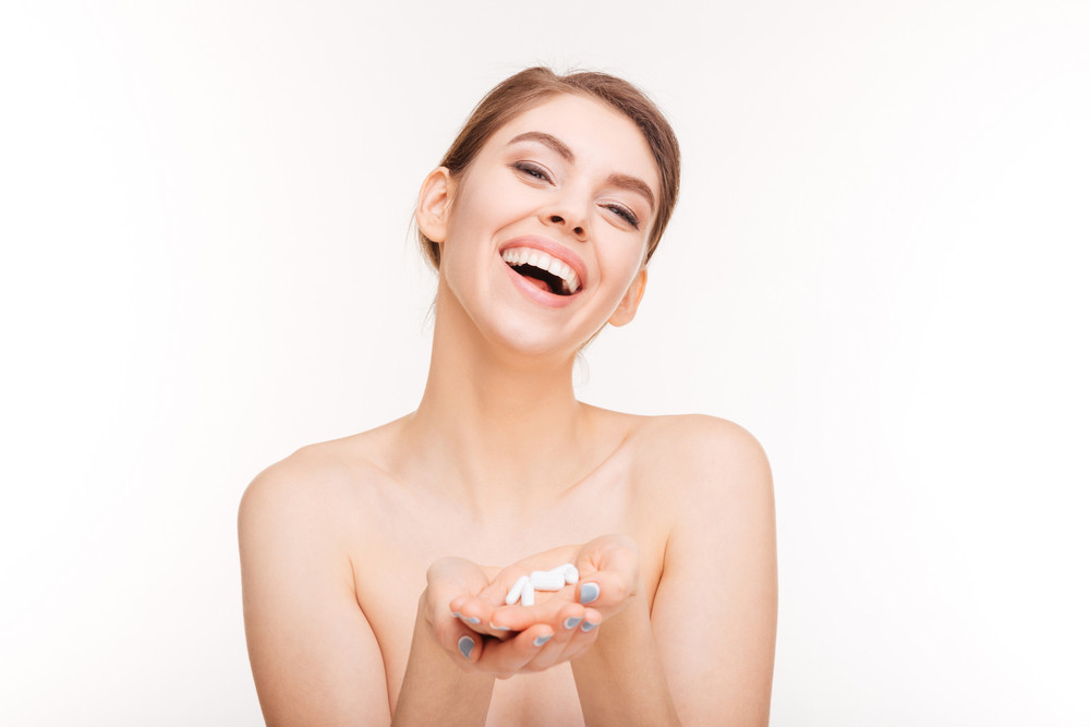 Beauty portrait of a laughing woman holding pills isolated on a white background