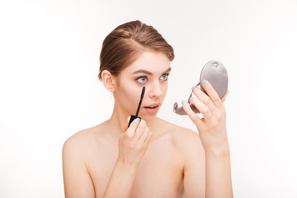 Beauty portrait of a young woman applying mascara on her eyelashes isolated on a white background