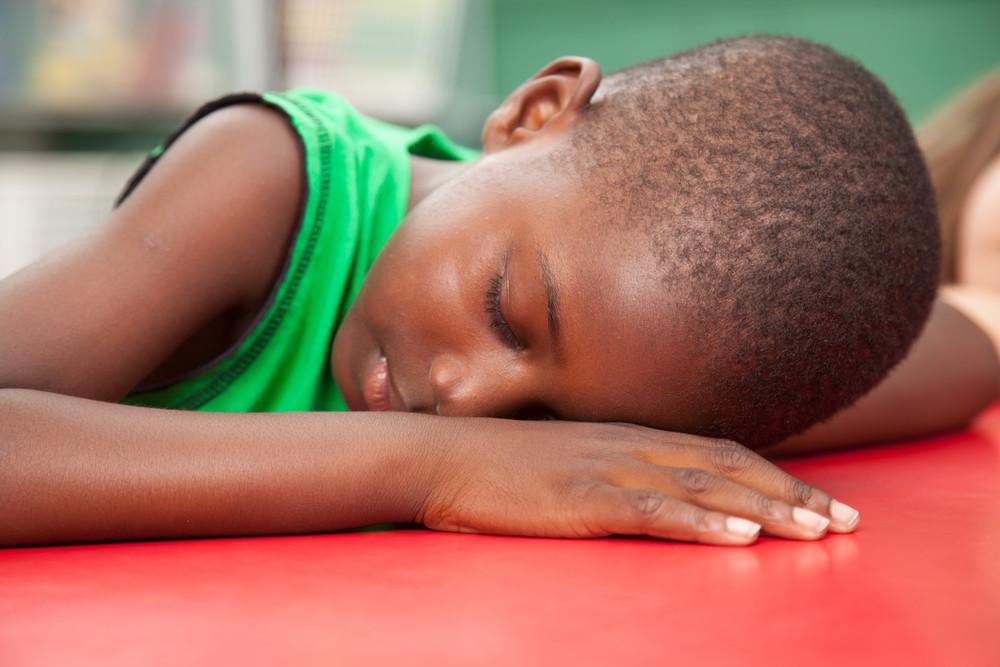 Black boy sleeping in kindergarten