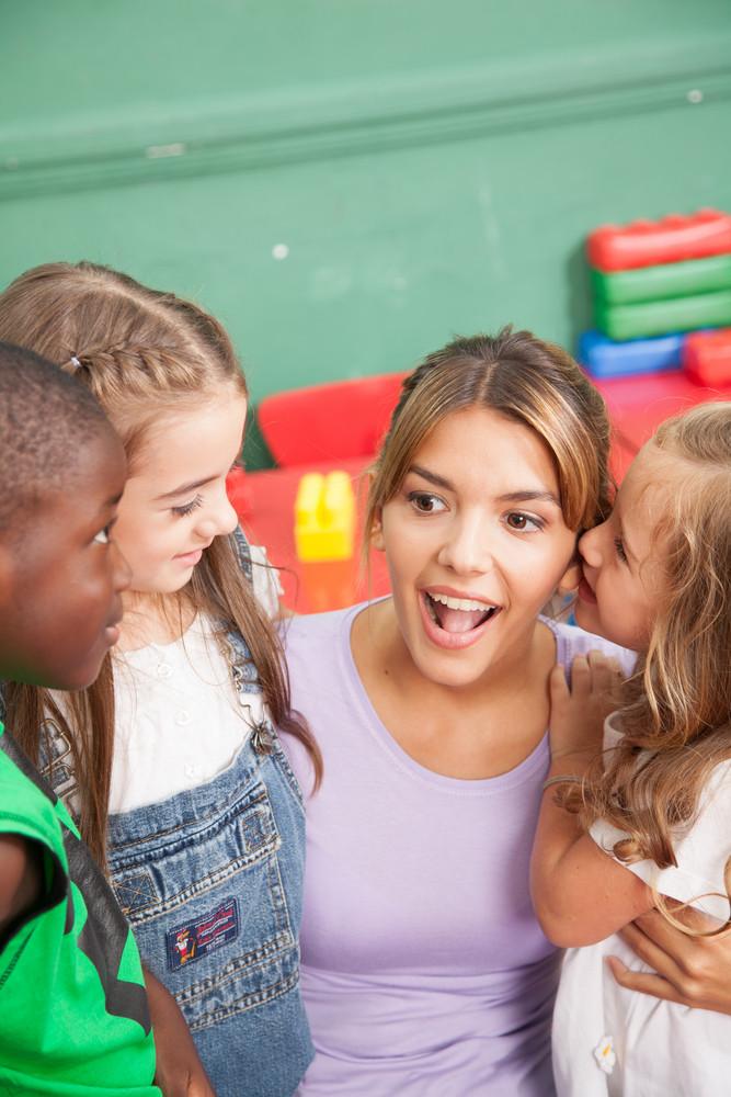 Black boy, two girls and teacher in  Kindergarten
