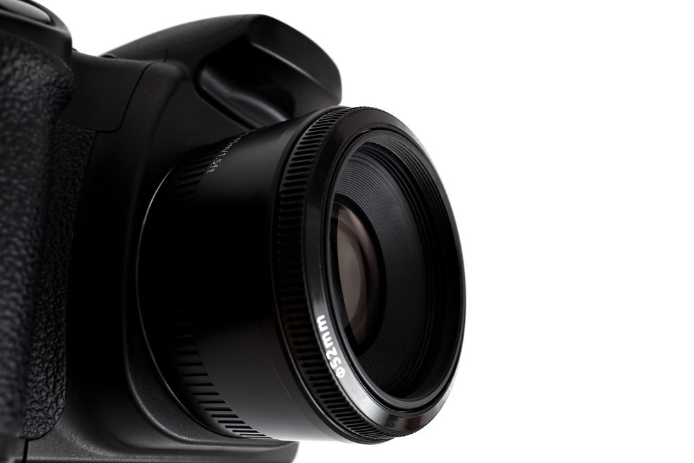 Black generic digital DSLR camera and attached lens isolated over white as seen from a dramatic angle.  Shallow depth of field.