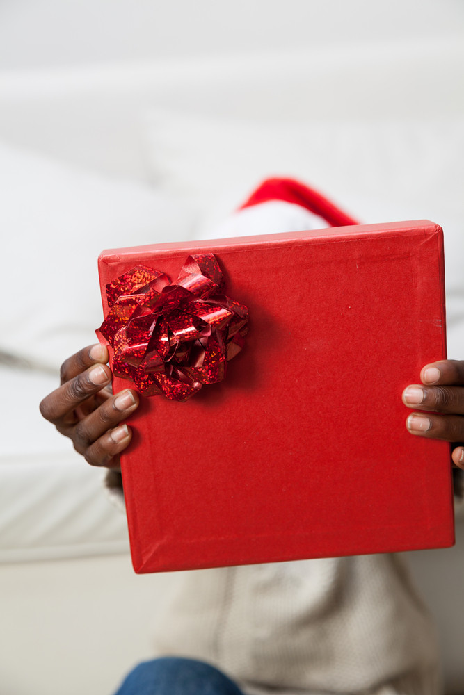 Black man covering his face with gift