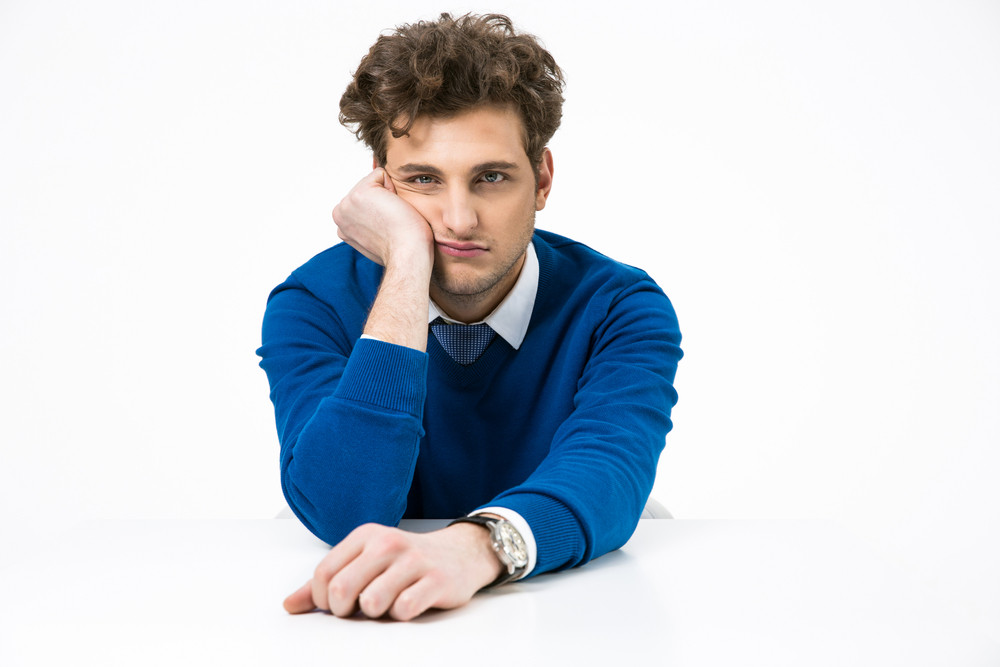 Bored businessman sitting at the table over white background