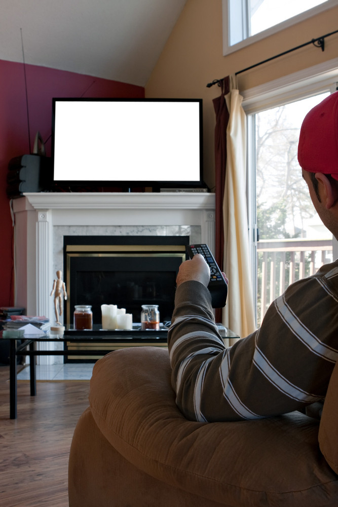 Bored man watches a big screen flat panel TV in his living room. Screen space on the plasma set has empty white copy space ready for your text or image.