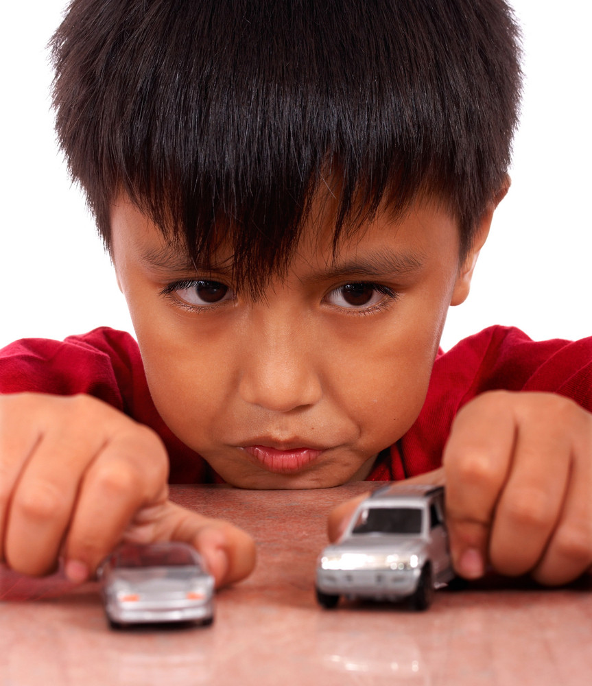 Boy Playing With Toy Cars On A Table