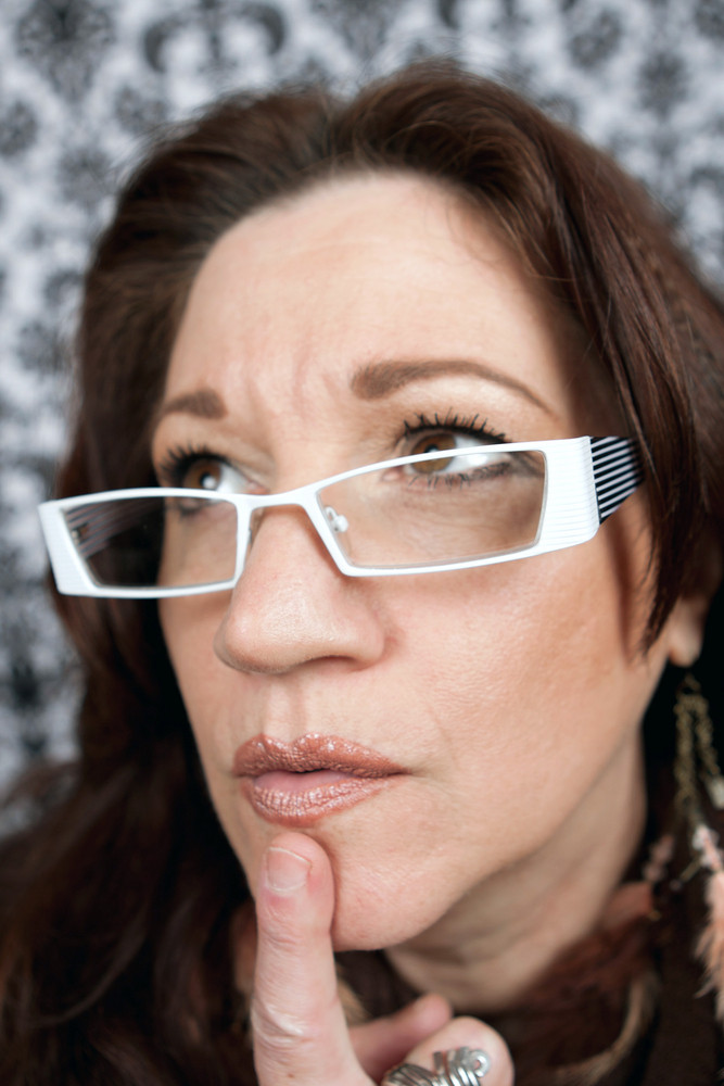 Brunette middle aged woman wearing white framed glasses with her finger on her chin in deep contemplation.  Shallow depth of field.