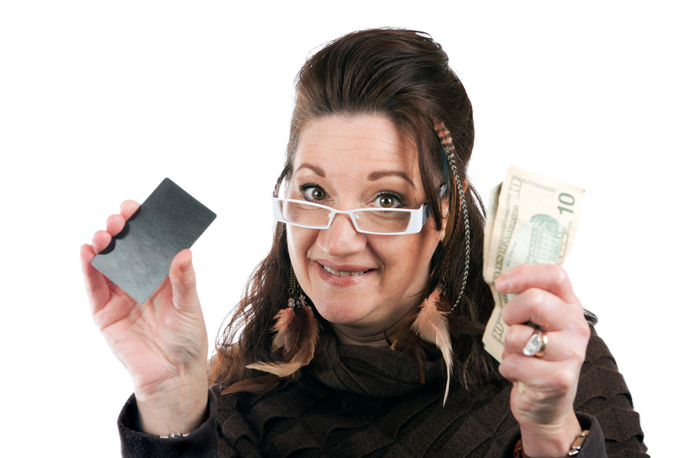 Brunette woman holding up a blank credit card business card shoppers club card or gift card of some sort along with some cash in her other hand.