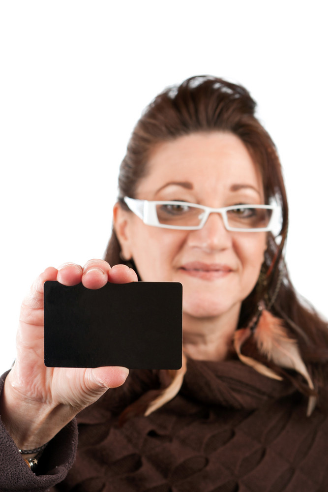 Brunette woman holding up a blank credit card business card shoppers club card or gift card of some sort with copyspace. Shallow depth of field.