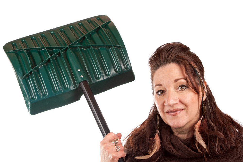 Brunette woman holding up her snow shovel isolated over a white backdrop.